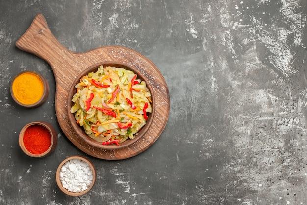 Top nahaufnahme salat salat gemüsesalat in der schüssel auf dem brett drei arten von gewürzen