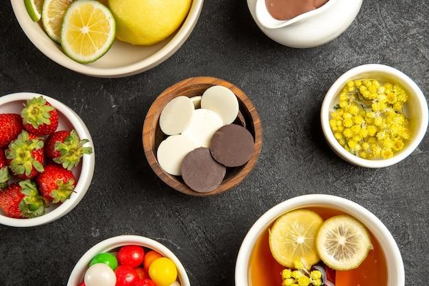 Top nahaufnahme schokoladen- und erdbeerschalen mit schokoladenkräutern und erdbeeren neben der tasse kräutertee auf dem dunklen tisch