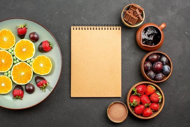 Top nahaufnahme schokoladensauce sahnenotizbuch zwischen erdbeerschokolade in schalen und teller mit kuchen mit schokoladensauce auf schwarzem hintergrund