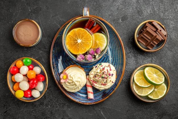 Top nahaufnahme süßigkeiten auf dem tisch schalen mit limetten und süßigkeiten neben der untertasse von zwei cupcakes und die tasse tee mit zimtstangen und zitrone auf dem tisch