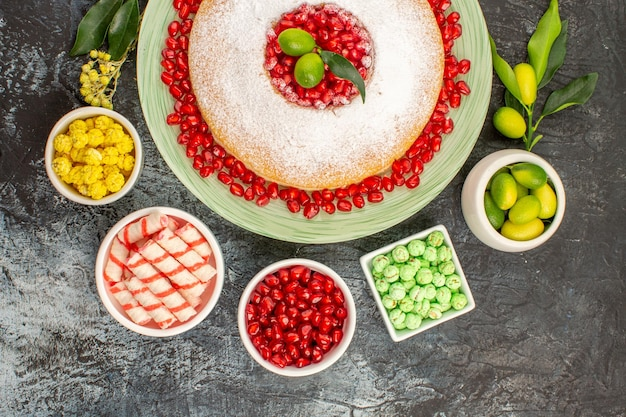 Top nahaufnahme süßigkeiten ein appetitlicher kuchen drei schalen limetten süßigkeiten granatapfelkerne