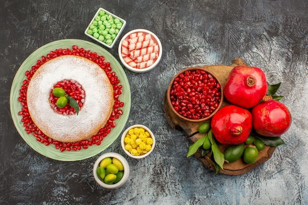 Top nahaufnahme süßigkeiten ein appetitlicher kuchen schalen mit süßigkeiten neben den granatäpfeln auf dem brett