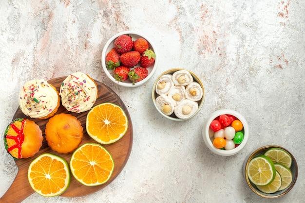 Top nahaufnahme süßigkeiten in schalen vier schüsseln mit süßigkeiten turkish delight und in scheiben geschnittene limette und das holzschneidebrett mit keksen und orange auf dem tisch