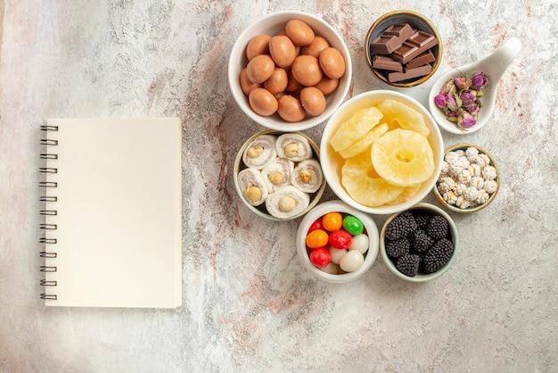Top nahaufnahme süßigkeiten in schüsseln weißes notizbuch neben den schüsseln mit verschiedenen süßigkeiten getrocknete früchte und beeren auf dem tisch