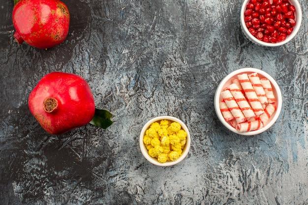 Top nahaufnahme süßigkeiten schalen mit granatapfelkernen bunte bonbons zwei granatapfel