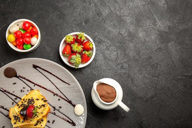 Top nahaufnahme süßigkeiten schüsseln mit süßigkeiten neben grauem teller mit kuchenstücken mit schokoladensauce und erdbeeren
