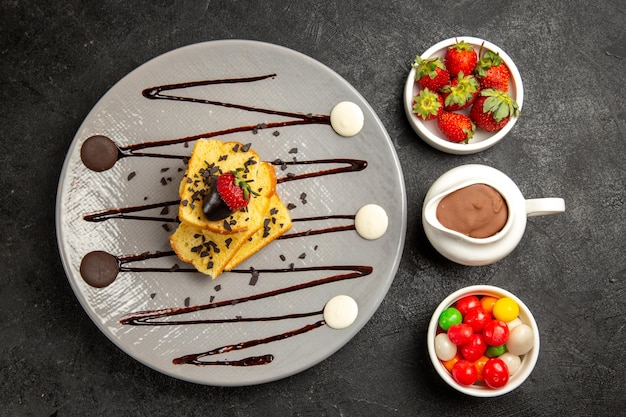 Top nahaufnahme süßigkeiten teller mit appetitlichem kuchen mit erdbeeren und schokolade neben den schalen mit erdbeeren bonbons und schokoladensauce