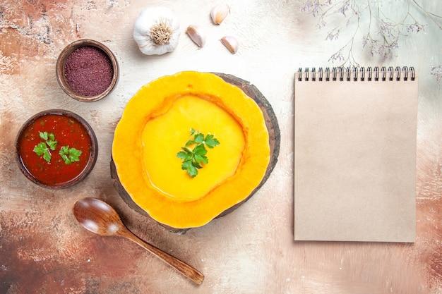 Top nahaufnahme suppe knoblauch löffel sauce gewürze kürbissuppe neben sahne notizbuch