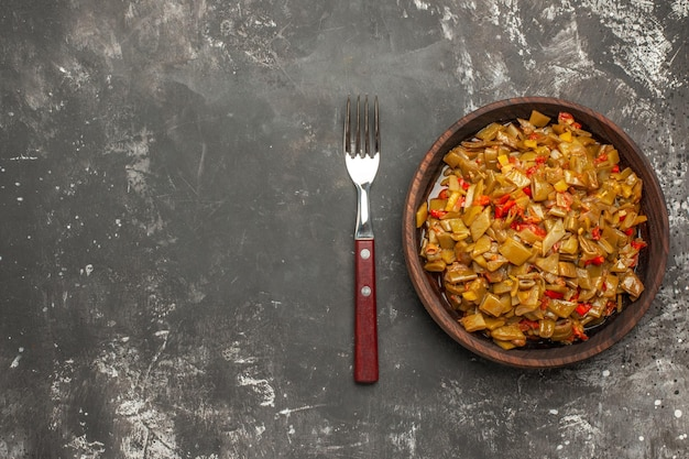 Top nahaufnahme teller mit grünen bohnen brauner teller der appetitlichen grünen bohnen und tomaten neben der gabel auf der rechten seite des dunklen tisches