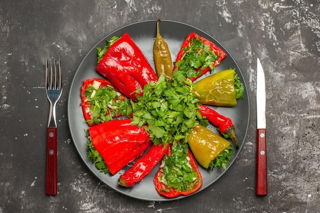 Top nahaufnahme teller mit paprika teller mit bunten paprika mit kräutern zwischen gabel und messer