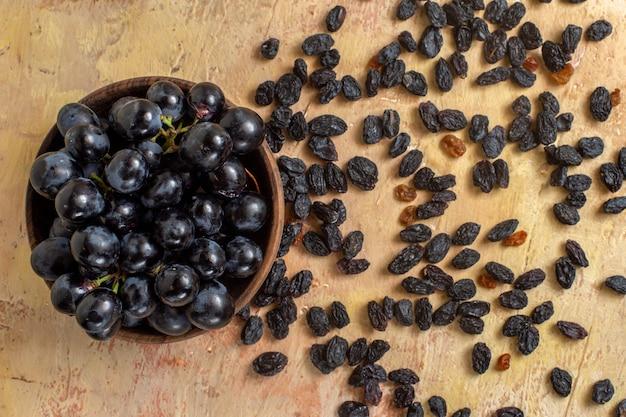Top nahaufnahme trauben schwarze trauben in der schüssel und rosinen