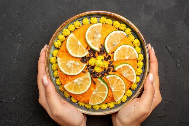 Top nahaufnahme zitrusfrüchte und schokolade appetitlicher kuchen mit zitrusfrüchten und schokolade in den händen auf dem schwarzen tisch
