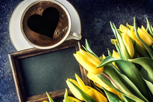 Top of view cup form kaffee mit herz leere tafel und frühlingstulpen auf holztisch.
