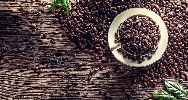 Top of view tasse voller kaffeebohnen auf rustikalem eichentisch.