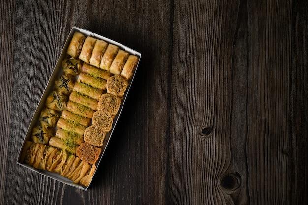 Top of view türkisches baklava süßes gebäck mit box isolierten hölzernen hintergrund