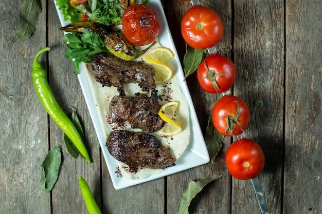 Top-rindfleisch-kebab, serviert mit zwiebeln, gegrillter tomate und pfeffer auf einer platte