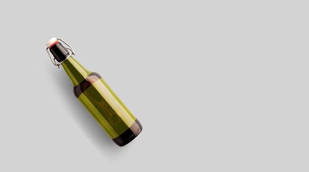 Top-up-ansicht braune bierflasche mit leerer gelber vorlage auf grauem hintergrund isoliert. bier-fiesta-konzept.