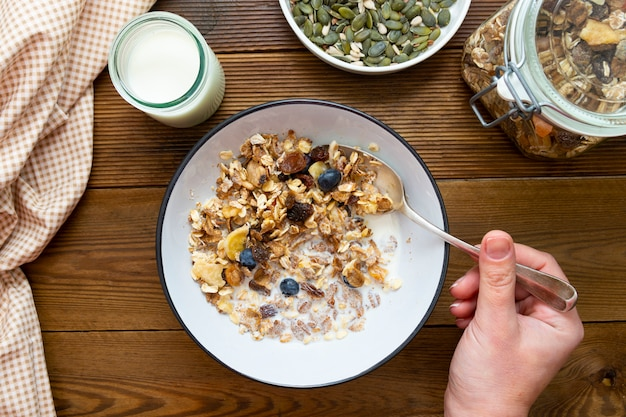 Top vie hand hält löffel hafer zum frühstück, müsli mit getrockneten früchten und blaubeeren, milch und honig.