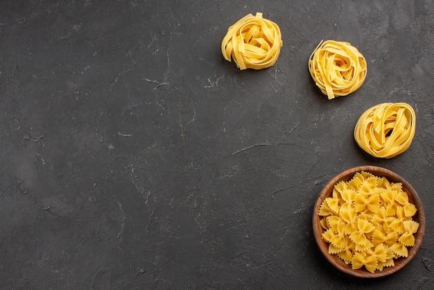 Top vie pasta in schüssel schüssel mit verschiedenen pastasorten auf der rechten seite des dunklen tisches
