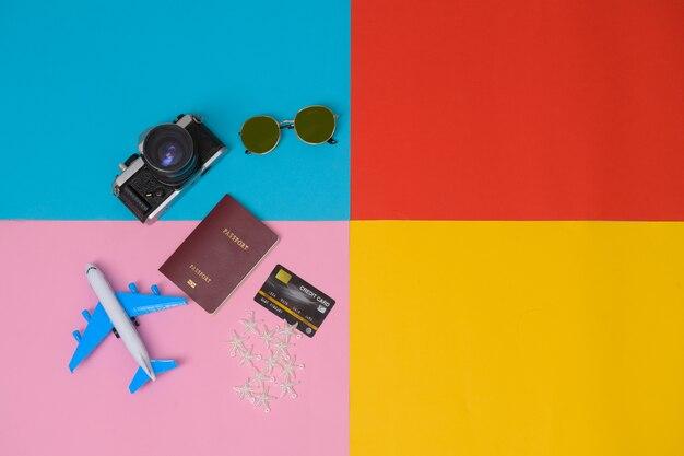 Top view artikel und zubehör für die reisenden mit reisepass, kamera, sonnenbrille, touristischen grundlagen. urlaubskonzept planen.