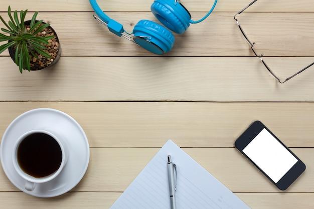 Top view briefpapier, kopfhörer, smartphone, stift, kaffee, kaktus, brillen auf büro schreibtisch hintergrund.