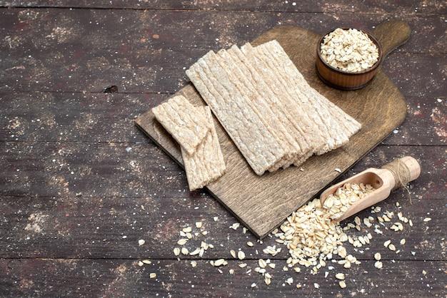 Top view chips und cracker lange mit rohem haferflocken auf holz schreibtisch geformt
