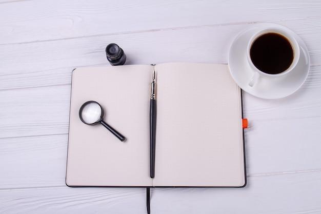 Top view copybook mit glaslupe und tasse kaffee.