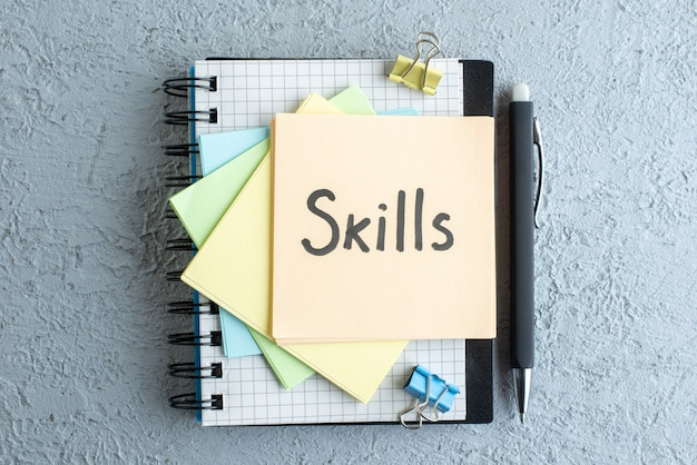 Top view fähigkeiten geschriebene notiz mit stift und notizblock auf weißem hintergrund job büro schule copybook gehalt college business farbe