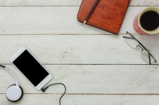 Top view / flat legen sie den stift / notizbuch / weißes mobiltelefon / radiohörer mit kopfhörern / schwarzem kaffee und brille auf rustikalem tisch aus holz.eine idee, zeit / ruhe zu entspannen oder eine pause zu machen.
