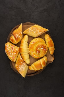 Top view gebäck zusammen mit croissants auf dem dunklen boden