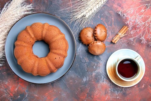 Top view kuchenplatte mit kuchen cupcakes eine tasse tee zimtstangen und weizenähren