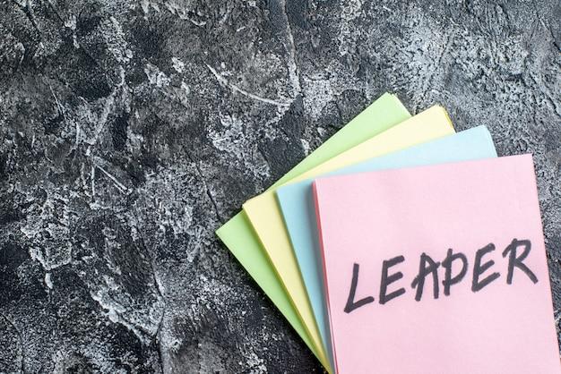 Top view leader schriftliche notiz mit aufklebern auf grauem hintergrund