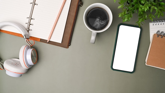 Top view mock-up handy, kopfhörer, kaffeetasse und notebook auf grauem hintergrund.