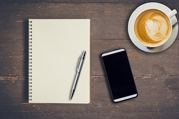 Top view notebook, kugelschreiber, kaffeetasse und telefon auf holztisch, vintage filter.