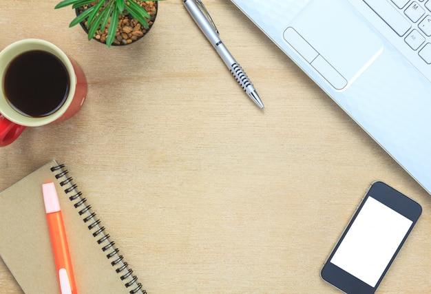 Top view notebook, stift, schwarzer kaffee, baum, notizpapier, smartphone, laptop, stationär auf büro schreibtisch hintergrund.