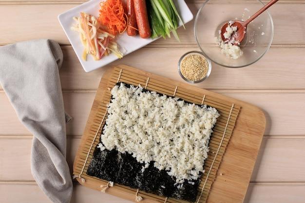 Top view process making gimbap (koreanischer rollreis). weißer reis (bap) gerollt mit nori algen oder laver mit verschiedenen zutaten wie karotte, kyuri (gurke), wurst, kimchi