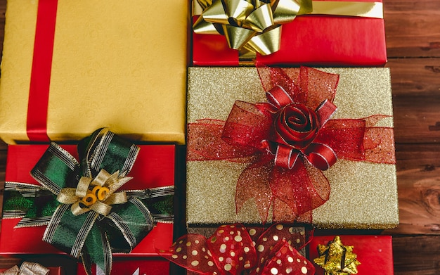 Top view studio shot muster aus buntem papier verpackt geschenkboxen mit gold-rot-grün und silber glänzend glänzenden bandfliege ordentlich auf dunkelbraunem holztisch in geburtstags- oder weihnachtsfeier platziert.