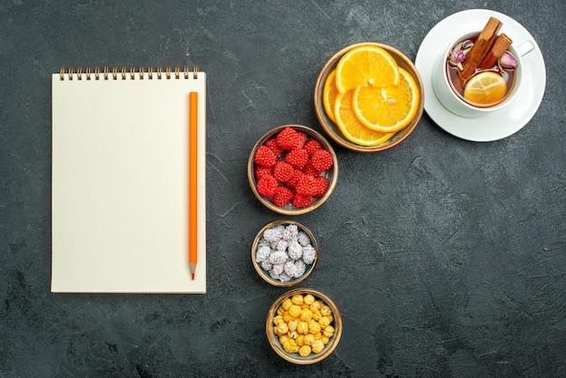 Top view tasse tee mit bonbons und orangenscheiben auf dunkler oberfläche konfitüre tee bonbon süß