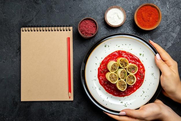 Top view teig mit fleisch in scheiben geschnitten mit tomatensauce und gewürzen auf der grauzone