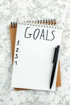 Top-view-zielliste auf notizblock geschrieben schwarzer stift auf grauem hintergrund