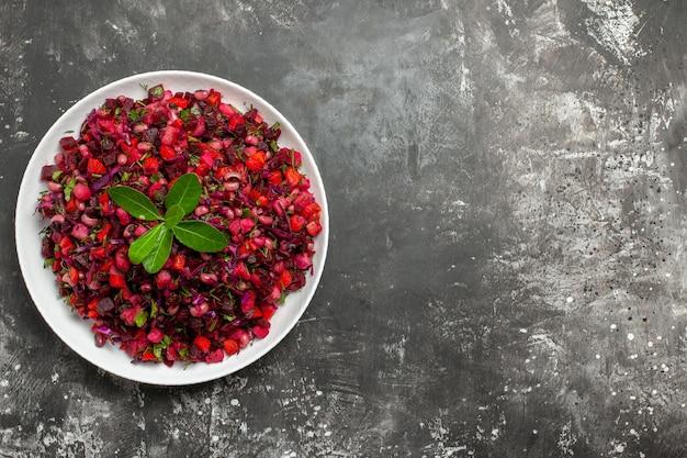Top viewo den linken salat mit rotem gemüse in einer weißen schale auf grauer oberfläche