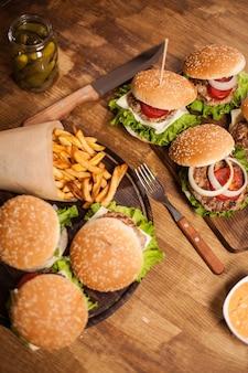 Top virew burger mit salat auf einem schneidebrett. fastfood. klassischer cheeseburger.