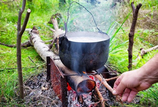 Topf auf dem feuer mit brennholz wirft hand