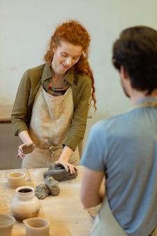 Topf herstellen. lächelnder langhaariger student im grünen hemd, der ein stück ton drückt, während er neue techniken in der töpferei lernt