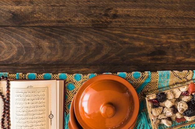 Topf in der nähe von koran und süßigkeiten