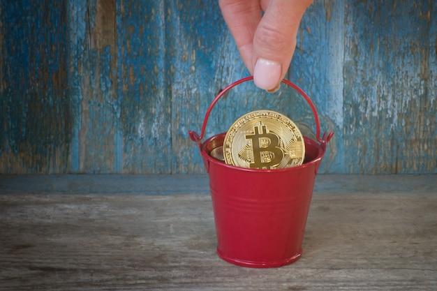 Topf mit goldmünze bitcoin in weiblicher hand. alter hölzerner hintergrund. unternehmenskonzept