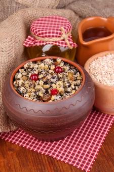 Topf mit kutia - traditionelles süßes weihnachtsessen in der ukraine, in weißrussland und in polen, auf holzoberfläche