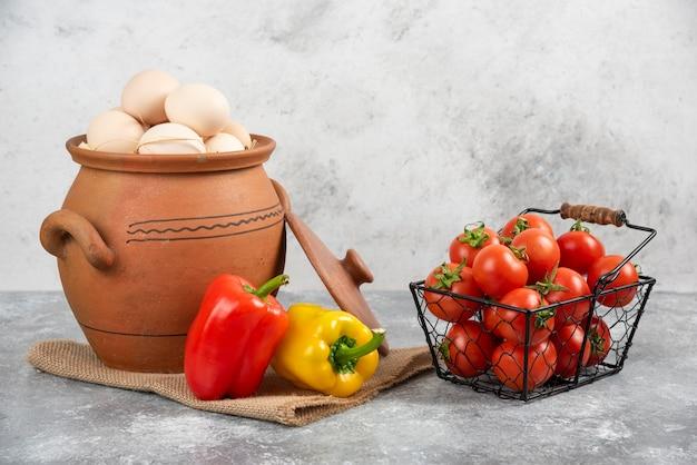 Topf mit rohen eiern, tomaten und paprika auf marmor.