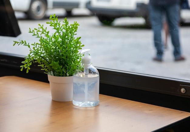Topfblumen und alkoholisches gel zur desinfektion auf einem tisch eines restaurants