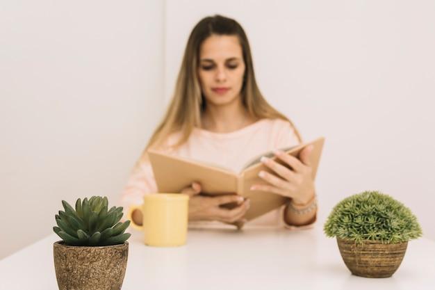Topfpflanzen in der nähe von frau zu lesen
